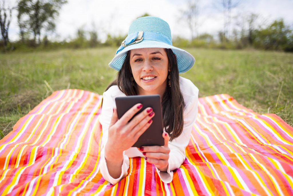 Young woman reading ebook on a blanket in the park.